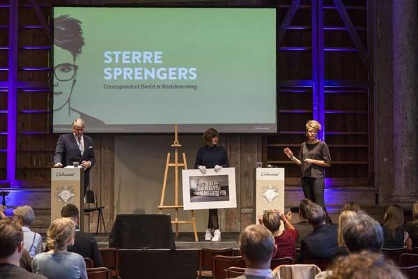 Onze Chef Beeld Sterre Sprengers (r) vertelt waarom het een goed idee is om een foto te kopen van Pieter van den Boogert. De veilingmeester wacht rustig af.