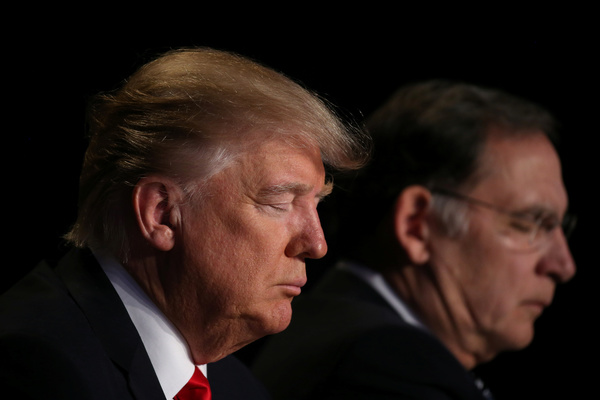 Een biddende Trump tijdens het National Prayer Breakfast (foto: Reuters)