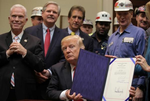Trump ondertekent een resolutie die milieubeperkingen voor de kolenindustrie opheft (foto: Reuters)