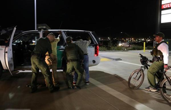 Amerikaanse grenswachten pakken twee Indiase immigranten op, nadat ze illegaal de Amerikaans-Mexicaanse grens zijn overgestoken bij Calexico (foto: Reuters)