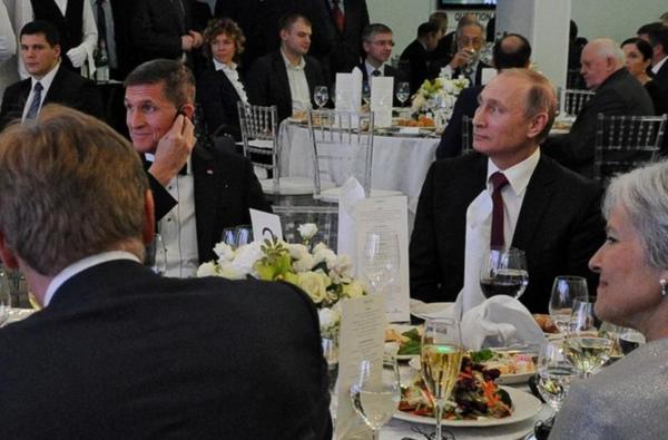 Michael Flynn (links) zit naast de Russische president Poetin tijdens een diner ter ere van het 10-jarige jubileum van de zender Russia Today (foto: Reuters)