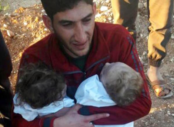 Een Syrische vader draagt zijn twee kinderen ten grave, die dinsdag omkwamen bij de gifgasaanval in Idlib