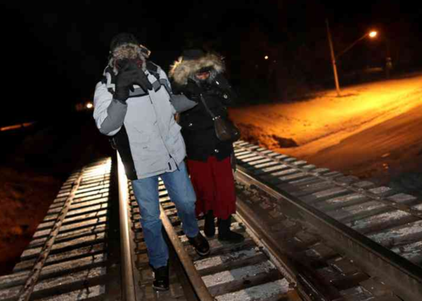 Vluchtelingen steken in het midden van de nacht de Amerikaanse-Canadese grens over (foto: reuters)