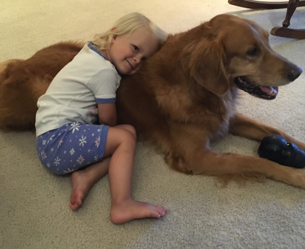 Hope, the daughter of loyal subscriber Anne, snuggles with her doggy companion, Tucker.