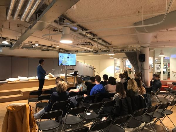 Monitor-collega Daan Jansen praat de studenten bij tijdens een presentatie.