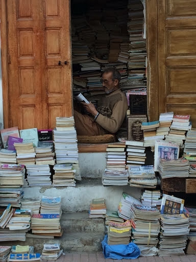 Loyal Reader #4 Erin taught at an elementary school in Morocco for two years. Here's her favorite bookseller inside his used bookstore stall in the Medina of Rabat. (Erin reports that selling books wasn't his top priority.)