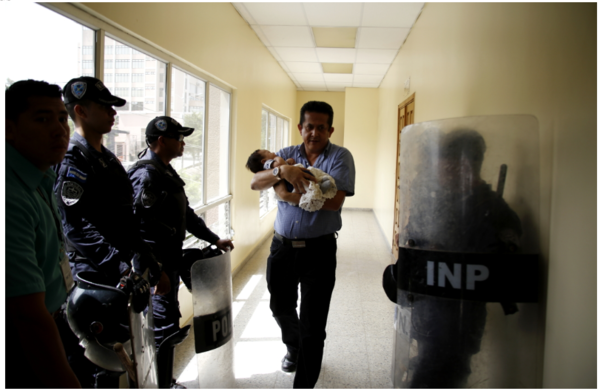 In Honduras, the brother of civil servant Velkis Hernández carries his niece in his arms while Hernández is at hearing for being implicated in Pandora corruption case. Photo: Martín Cálix/Contracorriente.