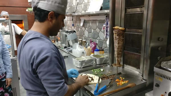 He slices beef off a vertical rotisserie and rolls it into a shawarma for Gabo.