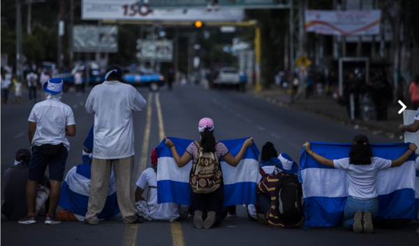 """Photo by Victor Peña for El Faro, in Managua, Nicaragua. Extract of his citation (translated by me): """"On Wednesday, September 26, members of Nicaraguan civil society - referred to by the local press as """"self-convoked"""" - had prepared a march from the Central American University (UCA) to the United Nations headquarters in Managua. However, as they were surrounded by anti-riot police forces and sympathizers of the Sandinista regime, they decided to turn the march into a 'sit-in'."""""""