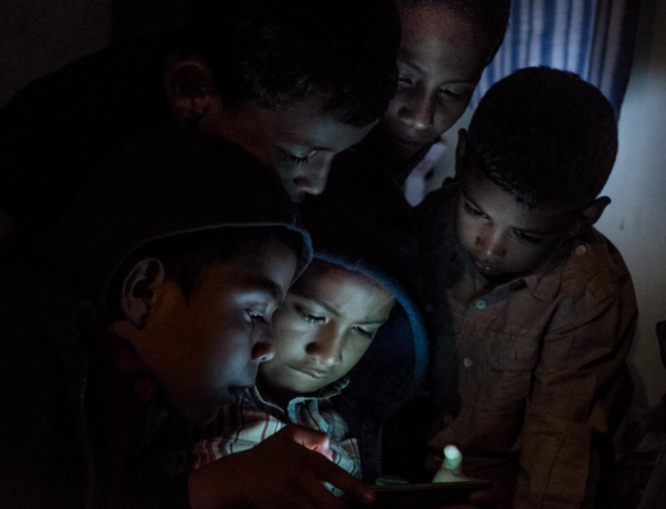 """""""Migdonio López, 8, Crisjon Rivas, 6, Brian Campos, 10, Tivinto Rivas, 9, and Sergio Hurtado, 9, are entertained by a video game on December 31, 2018. They had to go into exile with their parents [from Nicaragua] to Costa Rica."""" Photo credit: Fred Ramos/El Faro."""