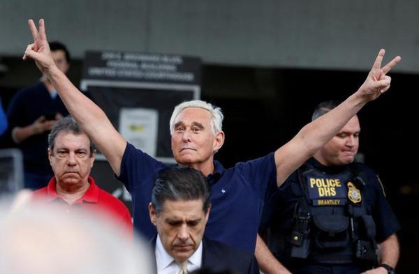 Roger Stone maakt een Nixoniaans V-gebaar bij het verlaten van de rechtbank (foto: Reuters)