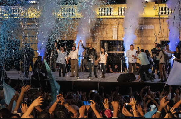 """""""Nayib Bukele, together with his wife Gabriela de Bukele and his running mate Félix Ulloa, say goodbye to the people who attended the Morazán Square to celebrate their triumph in the Salvadoran presidential elections on the night of February 3"""". Photo: Fred Ramos/El Faro."""