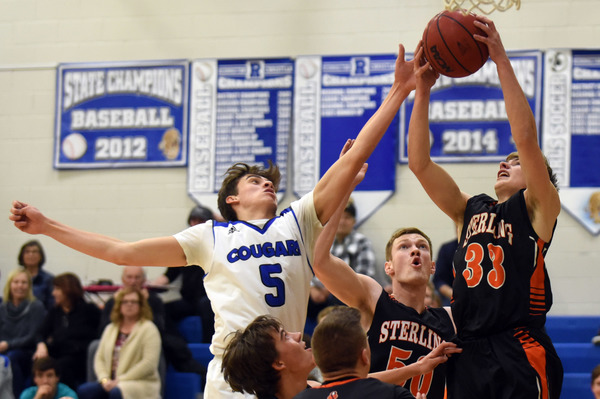 Resurrection Christian's Reece Johnson battles for a rebound with Sterling's Carter Keil on Jan. 15 at Resurrection Christian High School in Loveland. (Photo by Joshua Polson)
