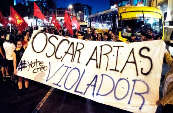 "People protest, holding a sign that read ""Oscar Arias rapist,"" against Nobel Peace Prize winner and former Costa Rican president Oscar Arias, who was accused of sexual assault in San Jose, Costa Rica February 8, 2019. Exequiel Becerra—AFP/Getty Images"