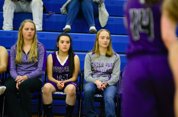 Estes Park's Ruth Walker, left, and Bella Walker, right, watch their team take on Resurrection Christian on Feb. 12 at Resurrection Christian High School in Loveland. The sisters tore their ACLs within three days of each other. (Photo by Quinn Ritzdorf)