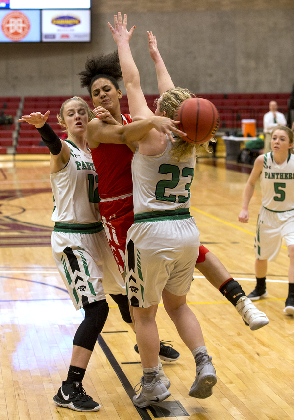 Eaton's Kaleigh Williams, middle, whips a pass around the defense of Delta's Keely Porter, right, during their 3A state tournament game Thursday in Denver. The Reds won 53-45 to move on to the next round. (Michael Brian/mbrian@greeleytribune.com)