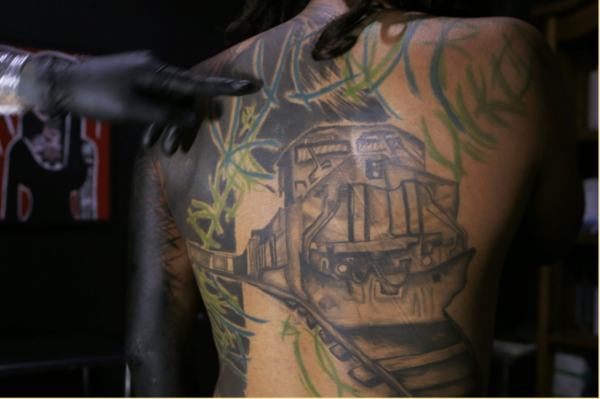 """In this Sept. 6, 2018 photo that was published on May 23, 2019, tattoo artist known as Enrique inks the image of the train known as """"La Bestia"""" on the arm of a migrant from El Salvador in Mexico City. The migrant wanted to memorialize one of his many trips on the train that took him from the Mexico – Guatemala border all the way north. (AP Photo/Marco Ugarte)"""