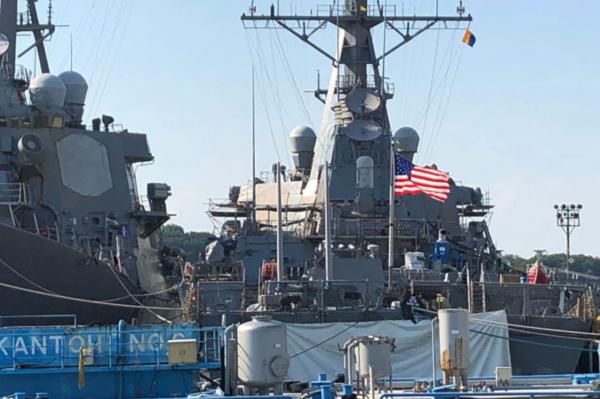 De naam van het Amerikaanse oorlogsschip USS John McCain werd afgedekt met een zeil om de president niet voor het hoofd te stoten (foto: WSJ)