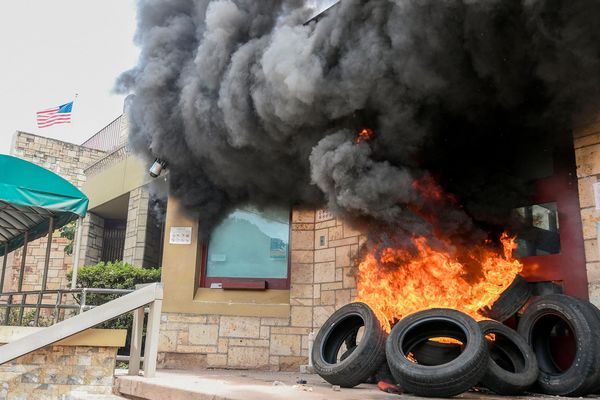 Tires burn at the entrance of the U.S. embassy in Tegucigalpa on May 31. Photographer: Orlando Sierra/AFP