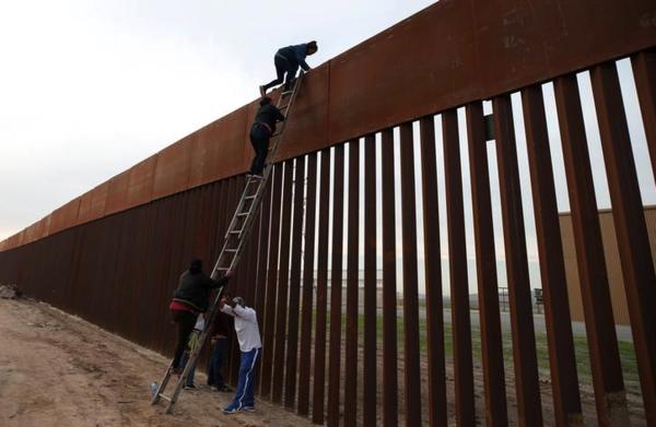 Migranten klimmen over het hek aan de Mexicaans`-Amerikaanse grens bij Tijuana (foto: Reuters)