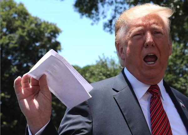 Trump zwaait met een papiertje waarop een geheime afspraak met Mexico zou staan (foto: Reuters)