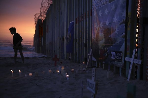 A youth stands by the border fence that separates Mexico from the United States, near a makeshift memorial for migrants who have died during their journey toward the U.S., in Tijuana, Mexico, late Saturday, June 29, 2019. On the border fence at right hangs a cartoon depiction of a news photograph of the bodies of Salvadoran migrant Óscar Alberto Martínez Ramírez and his daughter Valeria, photographed on the banks of the Rio Grande between Matamoros, Mexico, and Brownsville, Texas, after they drowned on Sunday, June 23. (AP Photo/Emilio Espejel)