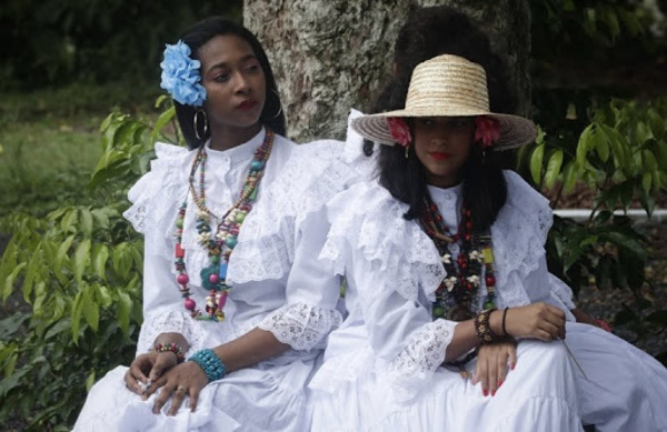 Women wearing Panamanian traditional dress rest under a tree near Fort San Lorenzo, on a bluff overlooking the mouth of the Chagres River, on Panama's Caribbean coast, Friday, June 28, 2019. The fort was built 1587 to protect the entrance to the river in the narrowest section of the Panama isthmus, used by the Spanish empire to protect the terminus of the Camino Real de Cruces that moved South American treasure from the pacific coast on its way to Spain. (AP Photo/Arnulfo Franco)