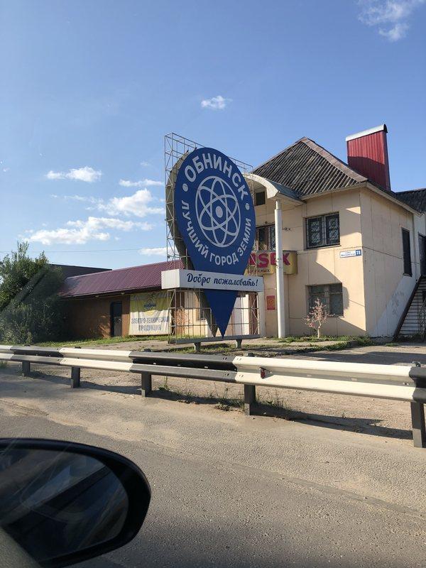 Надпись на знаке на въезде в город: Обнинск — лучший город земли. За ним — сексшоп.