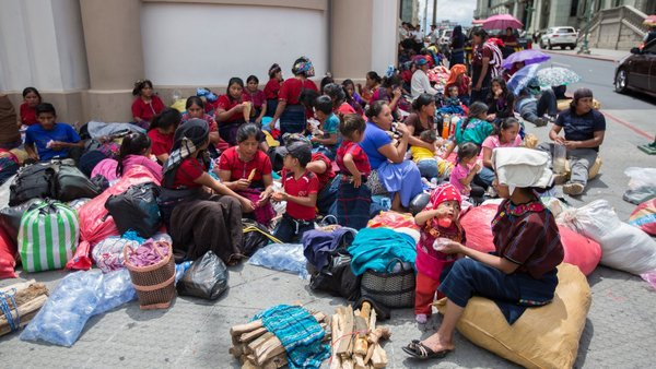 Residents from Cajolá, Quetzaltenango on the sidewalk outside Guatemala's presidential palace on August 6. The families state they intend to remain until the President follows through on an agreement for stolen land restitution. Credit: Jeff Abbott.