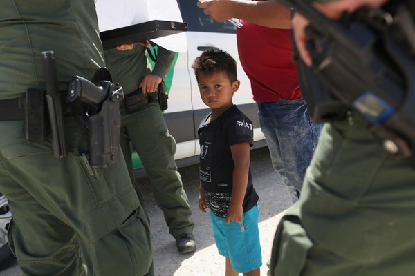"""Border Patrol agents take into custody a father and son from Honduras along the Mexico border on June 12 near Mission, Texas.(John Moore / Getty Images)"""