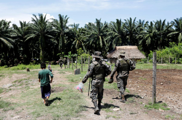 """Soldiers are seen near an African palm oil plantation run by NaturAceites during a temporary state of siege, approved by the Guatemalan Congress following the death of several soldiers in the area, in the village of Semuy II, Izabal Department, Guatemala September 9, 2019."" REUTERS/Luis Echeverria"