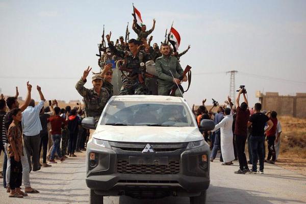 Syrische regeringstroepen trekken de grensplaats Ain Issa binnen, waar tot vorige week Amerikaanse troepen en Koerdische milities het nog voor het zeggen hadden (foto: Reuters)