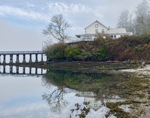 The Springwater Lodge reflecting in a still morning sea by Terrill Welch