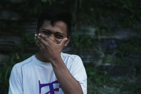 Youth from El Salvador covering his face while smiling. Photo Credit: Melissa Vida 2019.