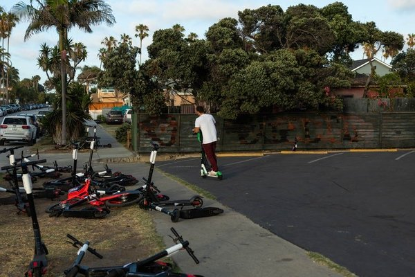 An e-scooter cemetery in Mission Beach, San Diego. A study published in August posited that whatever emissions electric scooters saved were offset by the greenhouse gas that gig workers expended chasing after scooters to perform maintenance and charging duties (link in picture).