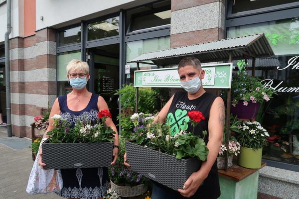 Die Blumenkästen sind fertig: Marlen Maciuga (l.) lässt den Balkon neu bepflanzen, um den Blumenladen von Anja Sprzagala (r.) nach der Schließzeit zu unterstützen. Foto: Jens Steglich