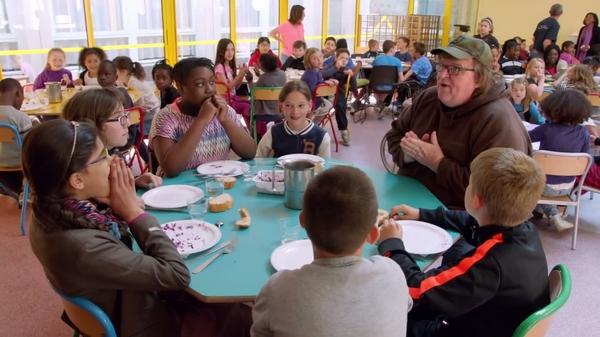 Michael Moore hablando con niños de un comedor de colegio en Francia