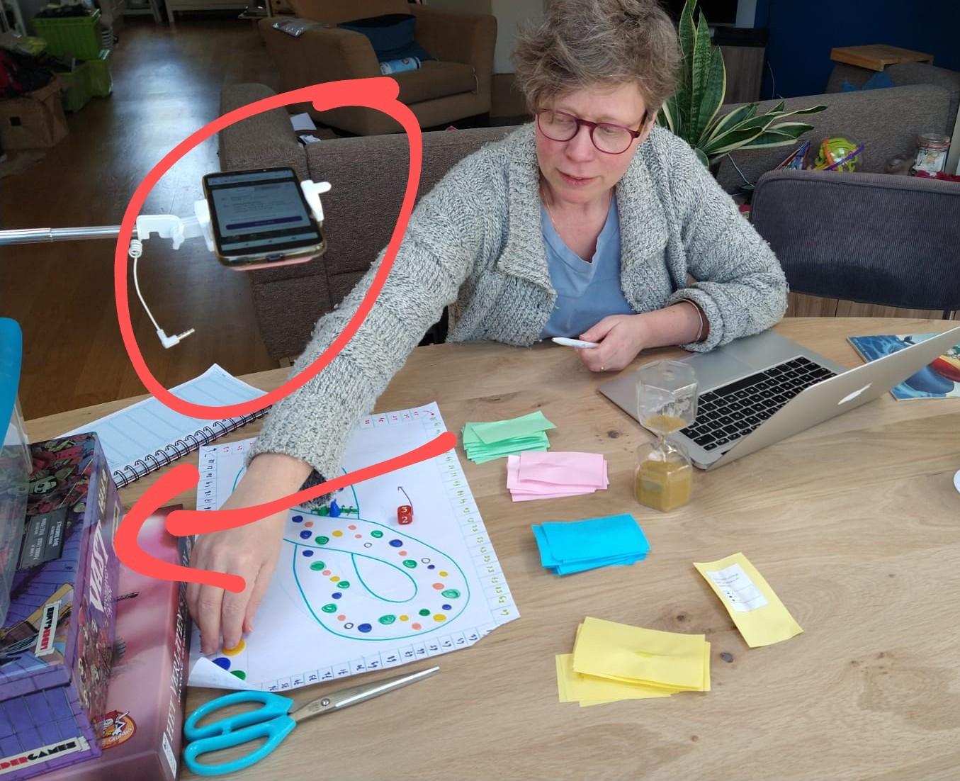Constructie met stapel spellen, selfiestick, gewicht en mobiel op derde scherm....