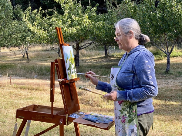 Jody Waldie painting in the morning light of an island orchard.