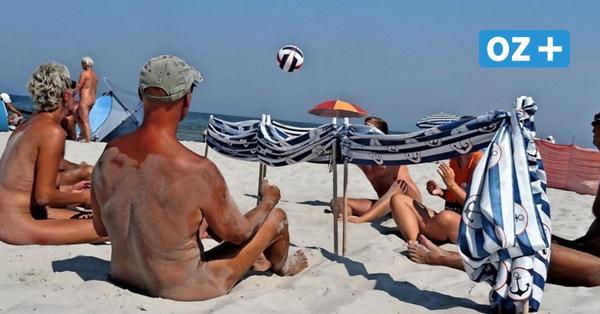 Nackideis spielen Beachvolleyball im Sitzen