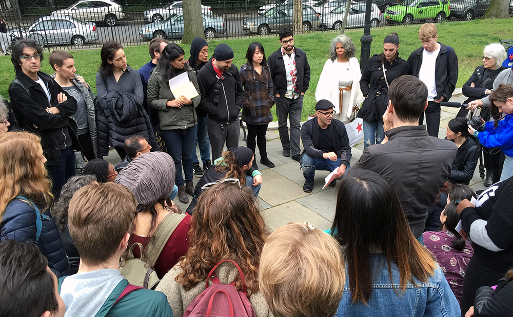 Amin Husain (crouching down in the center right) and Nitasha Dhillon (hold white papers in the center left) talking with a group of artists, activists, and locals before an action at the Brooklyn Museum in 2016. (photo Hrag Vartanian/Hyperallergic)