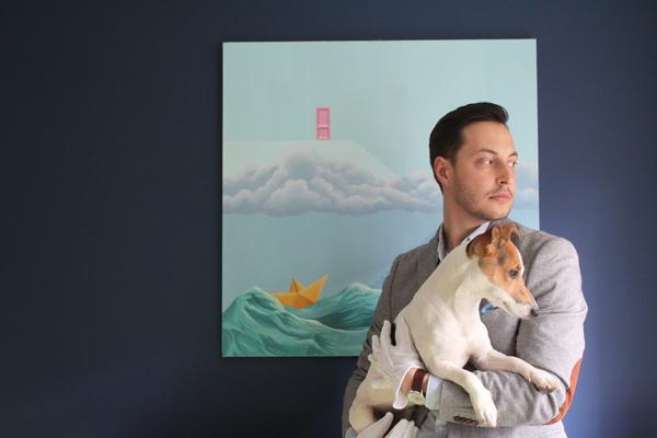 Łukasz Wiącek with his dog, Barry, in the background a painting by Miłosz Zawistowski