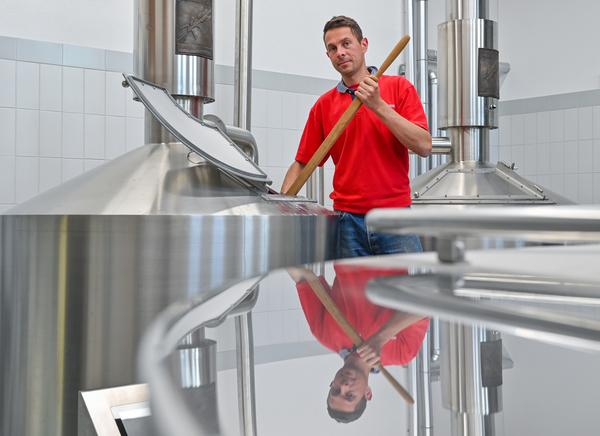 Brauingenieur Ruslan Hofmann steht zwischen dem Sud- und Gärbehälter in der Brauerei. Foto: Patrick Pleul