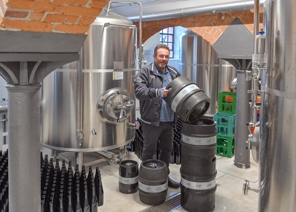 rank Dietrich steht hinter Bierfässern neben Lagertanks im Keller der Brauerei. Foto: Patrick Pleul
