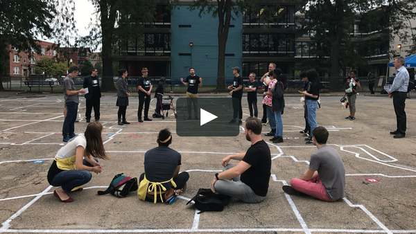 Image: A group of people gathered in a circle outside of a school. Some people are sitting on the ground, others are standing, and they all appear to be listening to one person speaking. There's a big play button overlaying the image, suggesting this is a still shot from a video.