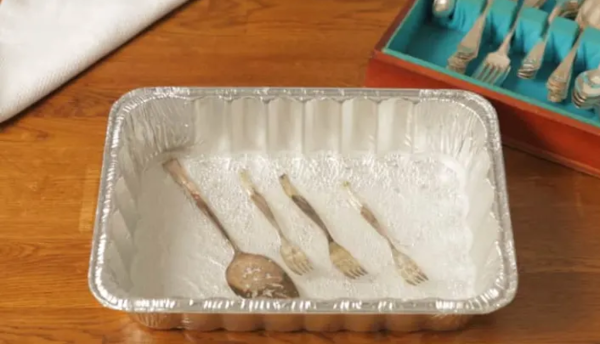 Cleaning silver with an aluminum baking pan, baking soda, salt, and boiling water.