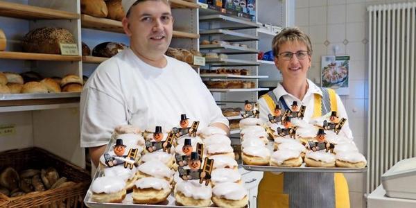 Bäckermeister Stefan Ober und Verkäuferin Ilona Anders stecken kleine Schornsteinfeger in ihre Pfannkuchen. Foto: Elinor Wenke
