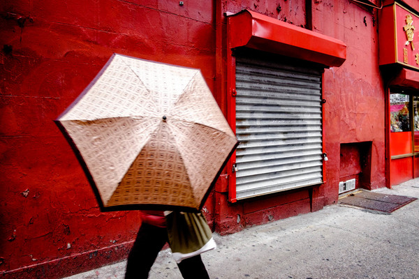 The joy of a red wall and of this woman moving her umbrella to hide her face from the camera! Umbrella Sideways, June 2018.