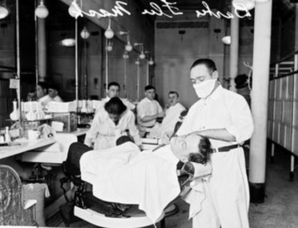 A Chicago barber wears a mask as he shaves a man's beard in 1918. Chicago Daily News