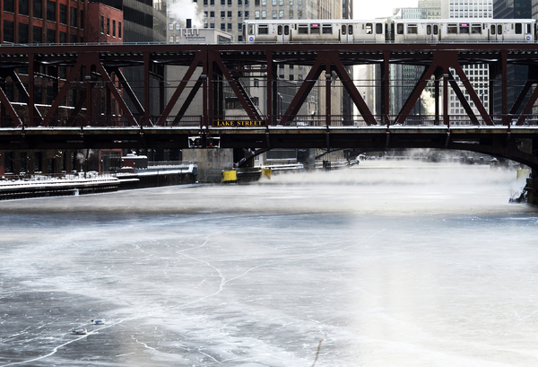 A pair of seagulls, lower left corner, rest on the iced over Chicago River at Wolf Point. | Craig Newman/Sun-Times